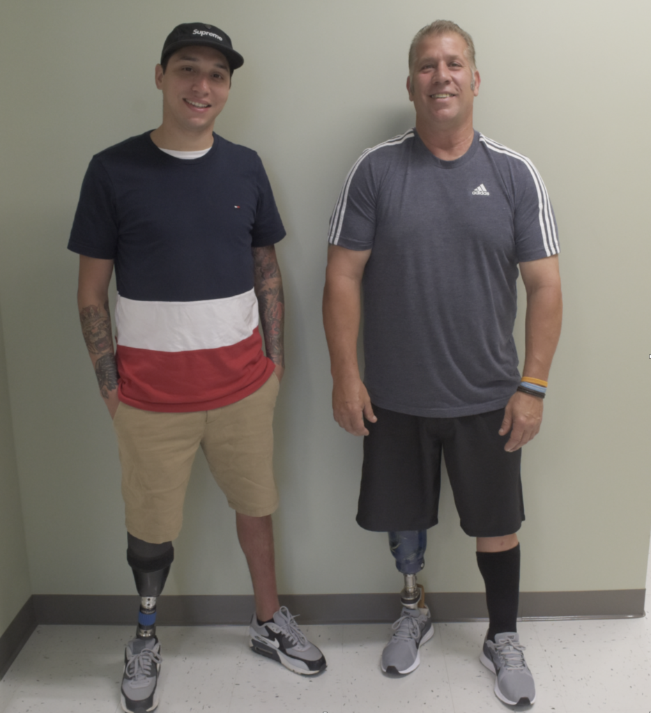 This is a photo of two men with prosthetic limbs posing for a photo.